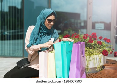 Beautiful muslim woman wearing hijab sitting on the bench near mall with purchases and talking by phone. Lucky shopping day concept