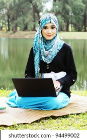 Beautiful muslim woman wearing scarf  with notebook at a lake garden