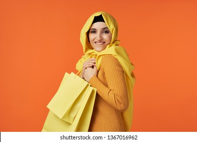 beautiful muslim woman in yellow hijab with shopping bags in hand orange background