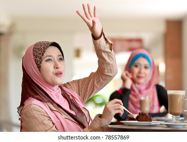 Beautiful Muslim women greeting friends whiles having lunch at coffee shop