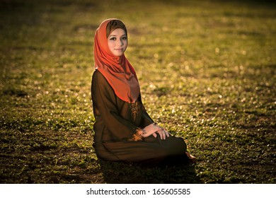 Beautiful muslimah lady sit and smile wear brown baju kurung