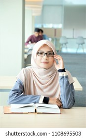 A beautiful Muslimah student with glass sitting in the library and smiling.