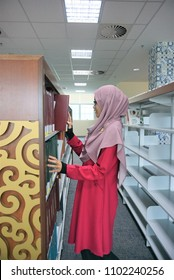 A beautiful Muslimah student  in library choosing books.