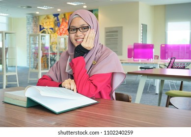 A beautiful Muslimah student sitting in the library and smiling.