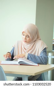 A beautiful Muslimah student sitting in the library with book open on the table