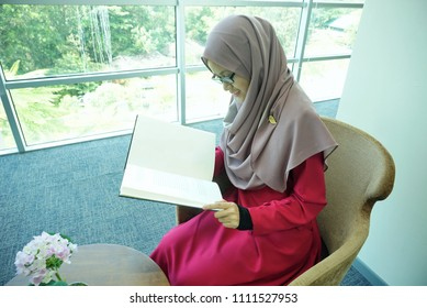 Beautiful Muslimah students are sitting by reading a book by the window