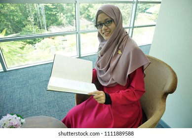 Beautiful Muslimah students are sitting and reading a book by the window with a smile looking ahead