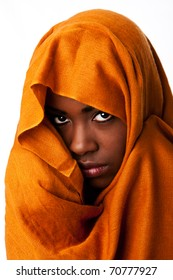 Beautiful mysterious african nomadic bedouin female face in ocher Earth tone head wrap scarf looking.
