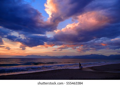 Beautiful mysterious dramatic romantic colorful sun dusk sunset on Ionian Sea on sand beach. Child and father parents. Twilight glow. Greece islands holidays