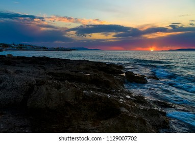 Beautiful mysterious marine landscape with resort town at sunset. Volcanic reef and ocean, Greek iseland Crete