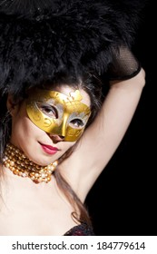 Beautiful and mysterious masked young woman on black background