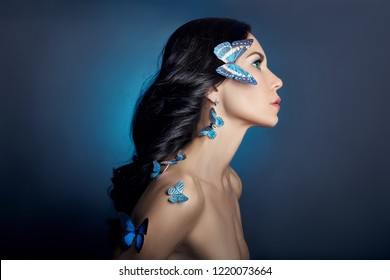 Beautiful mysterious woman with butterflies blue color on her face, brunette and paper artificial blue butterflies on the girls body. Bright green eyes, long black curly hair
