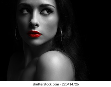 Beautiful mysterious woman in darkness looking dramatic with red lips. Closeup portrait on black background
