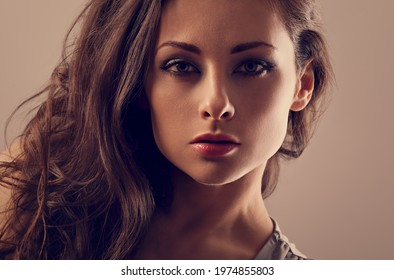 Beautiful mysterious woman makeup face and healthy volume brown hair with wisdom emotional look on brown color background with empty copy space. Closeup portrait