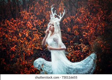 Beautiful mystery gothic woman in long white dress with deer horns in autumn forest. Dark fantasy creature elf in magic wood. Helloween dress style