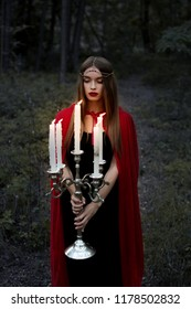 beautiful mystic girl in red cloak holding candelabrum with flaming candles in forest