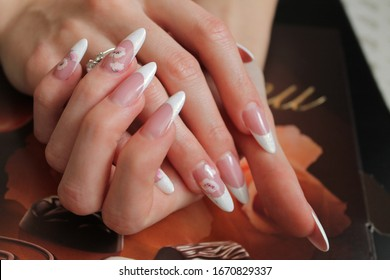 Beautiful nails of a young woman with long fingers and a beautiful French manicure with flowers