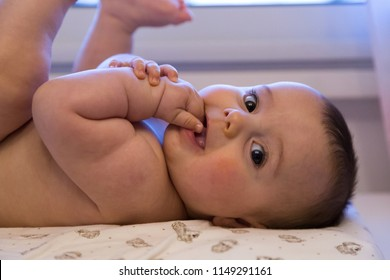 Beautiful naked baby waiting to be dressed.