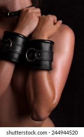 a beautiful naked body with leather handcuffs