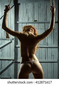 Beautiful naked body of young and sexy woman with tight tied hands in rope standing with buttocks