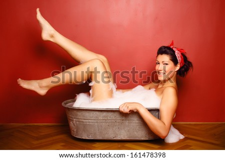 Nude girl bathing in tub with foam