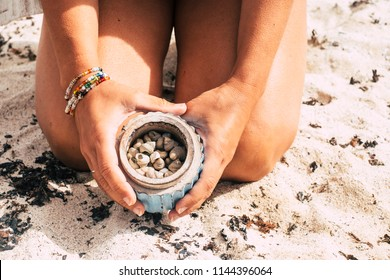 beautiful naked closeup image of woman body at the beach showing a box full of little shells. vacation and summer travel activity concept. nudism and lifestyle concept for people
