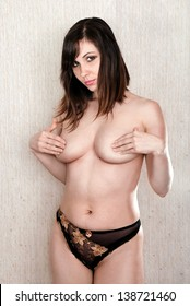 Beautiful naked girl covered with hands a breast.