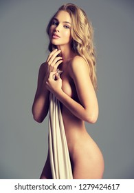Beautiful naked girl covers the naked breast. Gorgeous  woman with nude body. Nice portrait of a blonda girl with long curly hair.