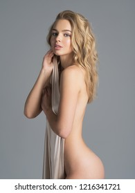 Beautiful naked girl covers the naked sexy body. Gorgeous  woman with nude body. Nice portrait of a blonda girl with long curly hair.