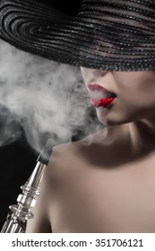 beautiful naked girl with red lips smokes hookah on black background
