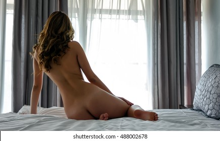Beautiful naked girl sitting on the bed and looking out the window at the morning sun.