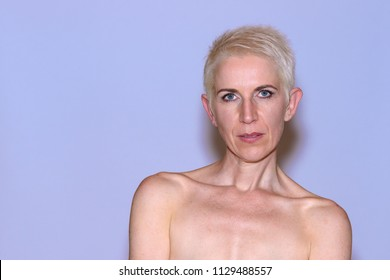 Beautiful naked mature woman with a thoughtful look