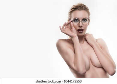 Beautiful naked shoulders young girl wearing round glasses portrait surprised covers her topless breasts with her hands isolated on white. Copy space. Advertising, conceptual and commercial design.