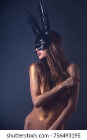 Beautiful naked woman in fashion bunny mask. Body covered with gold glitter