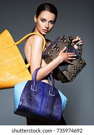 Beautiful naked woman holds fashion handbags. Girl model posing at studio. Fashionable person.