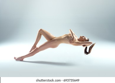 Beautiful Naked Woman Levitating Isolated On The Gray Background