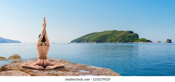 Beautiful Naked Woman Practicing Yoga Poses On Stone Outdoors During Daylight By The Sea
