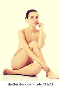 Beautiful naked woman sitting on the floor.