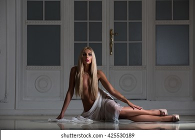 Beautiful naked woman sitting on the floor at night