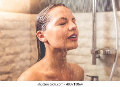 Beautiful naked woman is smiling while taking shower in bathroom