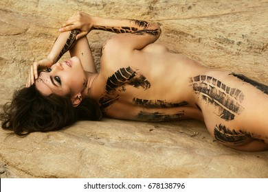 Beautiful naked woman with trace of car tire on her body is posing beside the sand cliffs