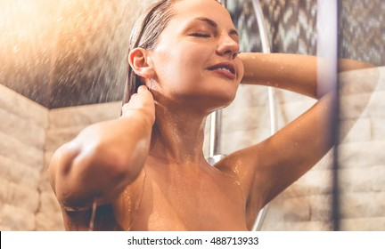 Beautiful naked young woman is smiling while taking shower in bathroom