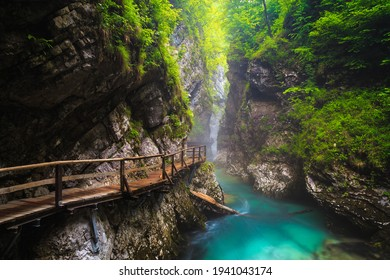 Beautiful narrow misty Vintgar gorge with wooden footbridge over the Radova river after summer rain. Fantastic hiking and touristic place, Slovenia, Europe
