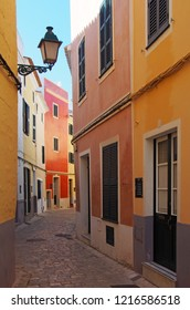 A beautiful narrow quiet street of brightly painted old houses in summer sunlight in ciutedella menorca