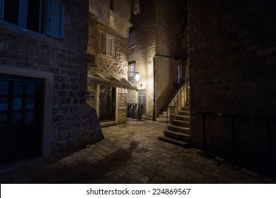 Beautiful narrow street of ancient city illuminated by lantern at night