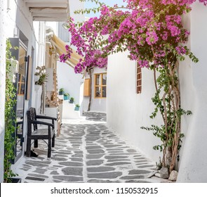 Beautiful narrow street with white houses in Mikonas island, Greece. Traditional narrow street with white facedes of buildings and blue doors