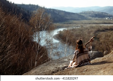 beautiful native indian american woman shaman  sitting on rocks and looking at woods and river
