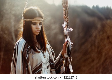 beautiful native indian american woman with warrior shaman make up looking and holding rod