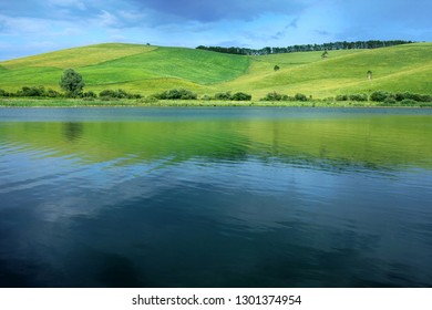 Beautiful natural background. Green hill, blue sky and blue water of the lake in Altai in Russia