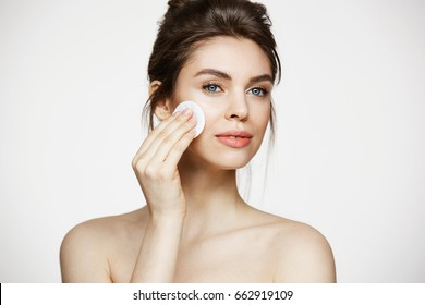 Beautiful natural brunette girl cleaning face with cotton sponge smiling over white background. Cosmetology and spa.